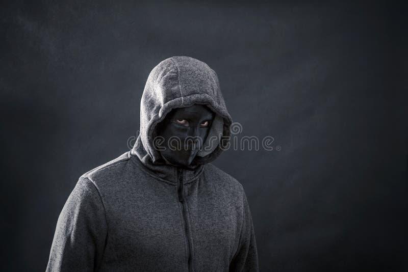 С капюшоном человек с черной маской стоковая фотография rf