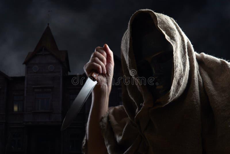 С капюшоном человек в маске с ножом стоковое фото rf