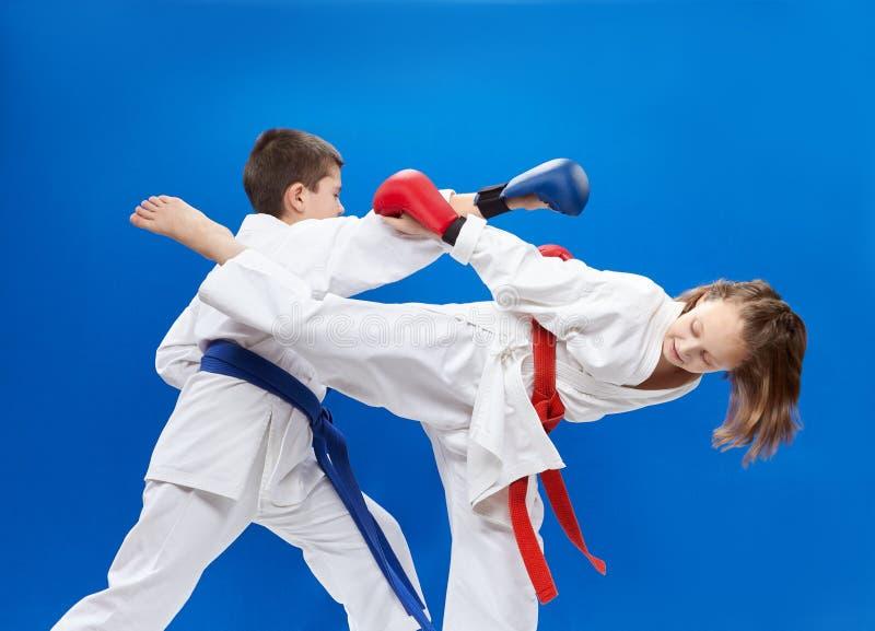 С красными и голубыми верхними слоями на его руках спортсмены тренируют блоки и рему стоковое фото rf