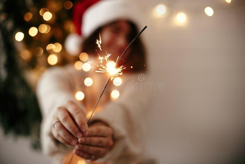 С Новым Годом! атмосфера партии кануна Горение бенгальского огня в руке стильной девушки в шляпе santa на предпосылке современной стоковая фотография rf