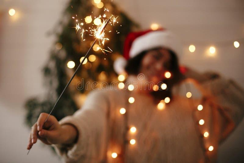С Новым Годом! атмосфера партии кануна Горение бенгальского огня в руке стильной девушки в шляпе santa на предпосылке современной стоковые изображения rf
