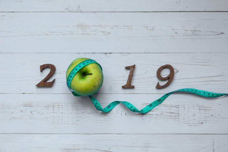 2019 С Новым Годом! для здравоохранения, здоровья и медицинской концепции зеленое яблоко, измеряя лента и деревянный номер стоковые фото