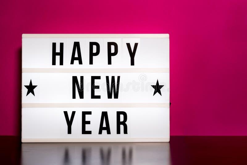 С Новым Годом! знак - литерность стиля кино на светлой коробке & горячей розовой предпосылке стоковое фото