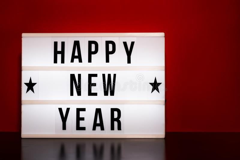 С Новым Годом! знак - литерность стиля кино на светлой коробке & теплой красной предпосылке стоковое изображение rf
