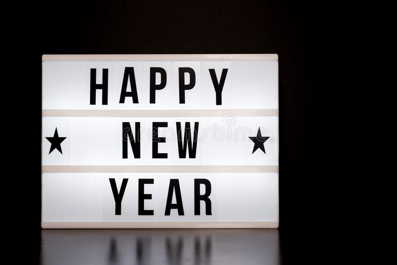 С Новым Годом! знак - литерность стиля кино на светлой коробке & черной предпосылке стоковые изображения