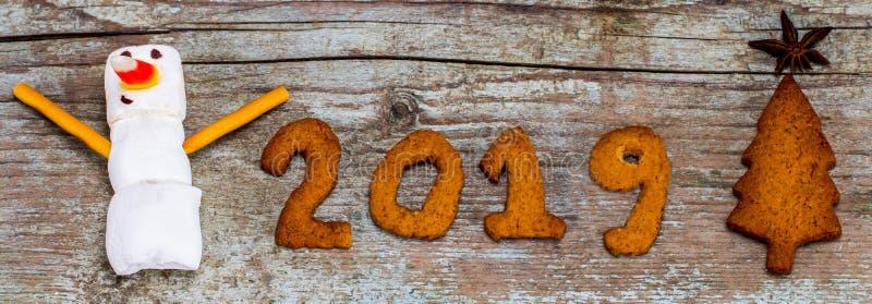С Новым Годом! концепция 2019 - смешной снеговик зефира и 2019 с пряником на деревянной предпосылке стоковая фотография