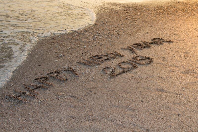 С Новым Годом! 2019, написанный в песке пишет на тропическом пляже с стоковые фото