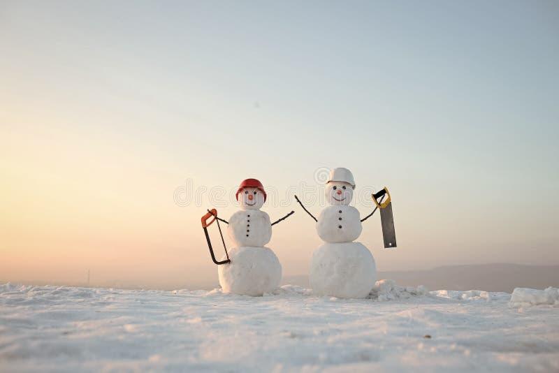 С новым годом с снеговиком Пары Snowmans счастливые Торжество Snowmans Построитель снеговика в зиме в шлеме стоковое изображение