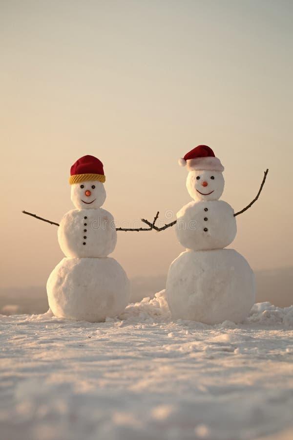 С новым годом с снеговиком Пары Snowmans счастливые Торжество Snowmans Шляпа Санта Клауса в зиме стоковые изображения rf