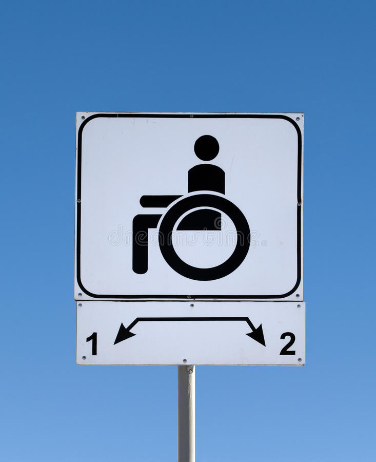 С ограниченными возможностями знак автостоянки на дороге стоковое изображение rf