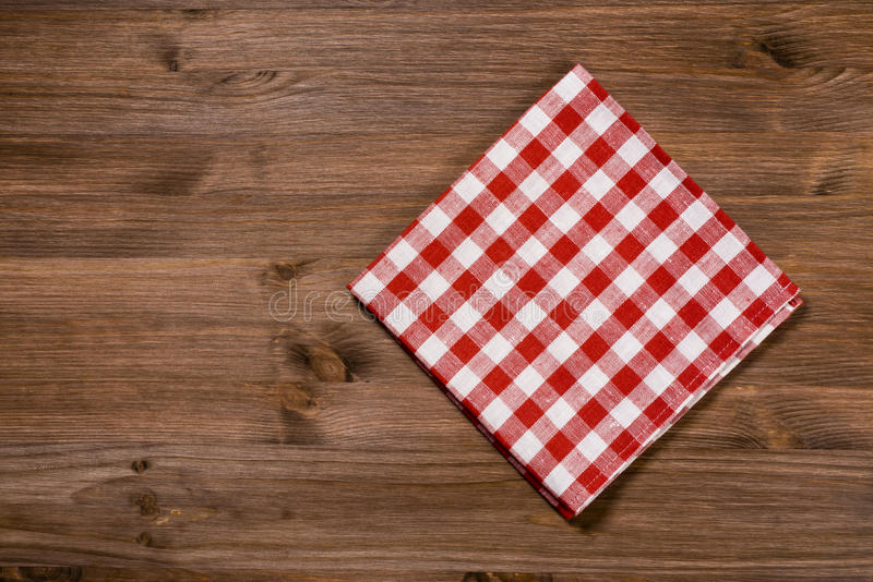 Сложенная красно-белая салфетка на деревянном столе стоковые изображения