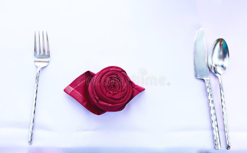 Сложенная розовая салфетка формы с ложкой, вилкой и ножом стоковое изображение rf