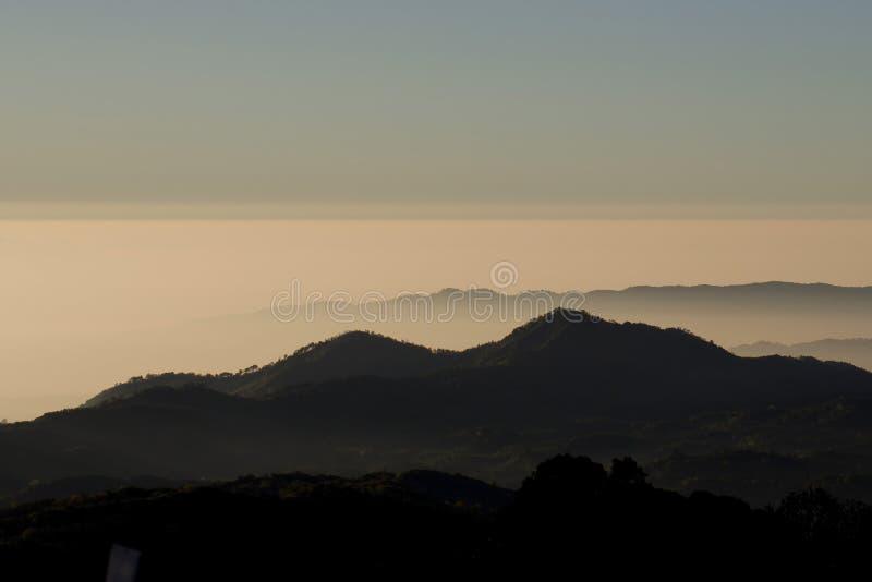 Слои гор и тумана на восходе солнца стоковые изображения rf