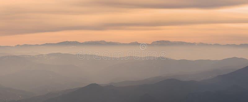 Слои красивых холмов в предыдущем утре fogy стоковые фото