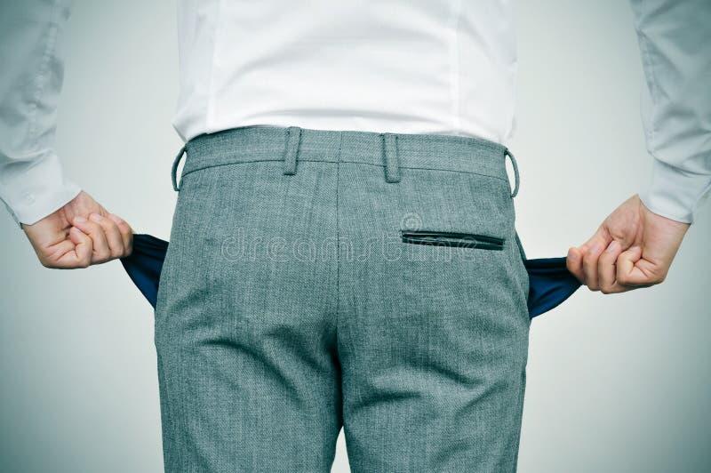 Сломал бизнесмена показывая его пустые карманн стоковое изображение