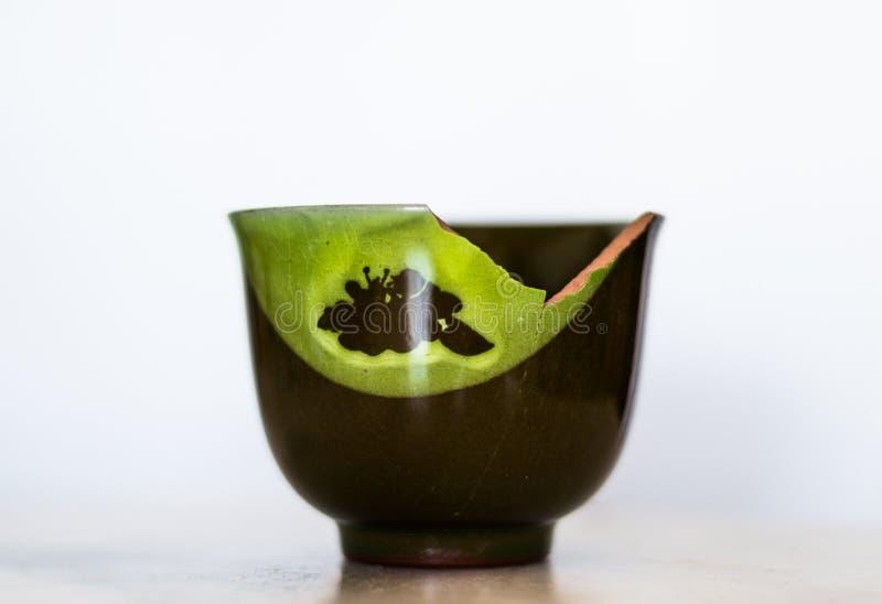 Сломленная зеленая керамическая чашка изолированная на белой предпосылке стоковая фотография