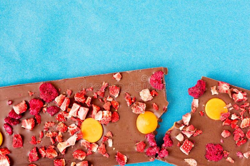 Сломленная таблетка молочного шоколада апельсина, клубники и поленики стоковые фотографии rf