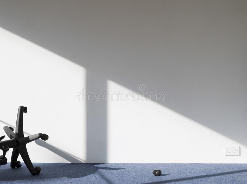 Сломленная тень отливки стула офиса на стене стоковая фотография rf