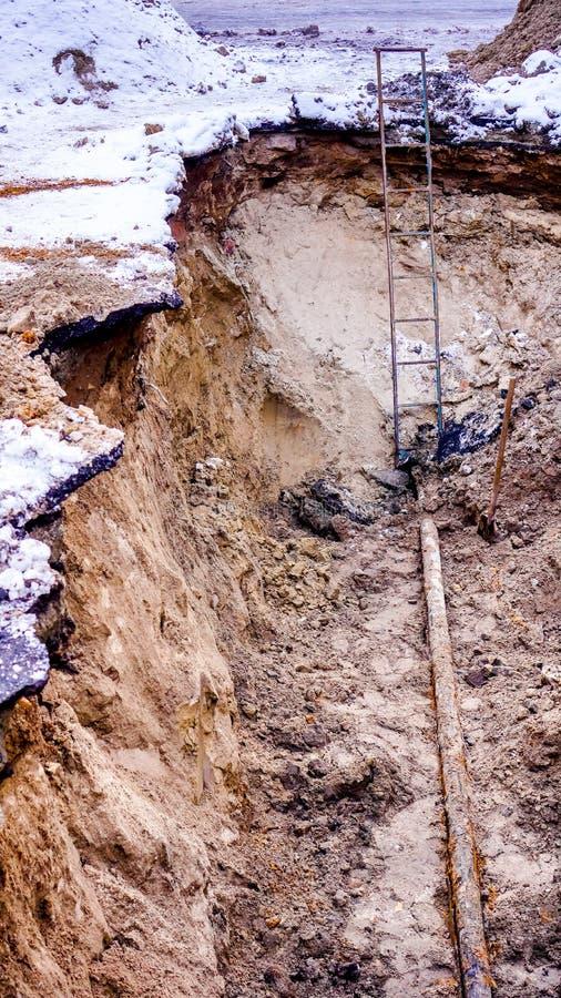 Сломленная труба грунтовой воды в большой глубокой яме с серым асфальтом под тонким carpetfd снега стоковые фото