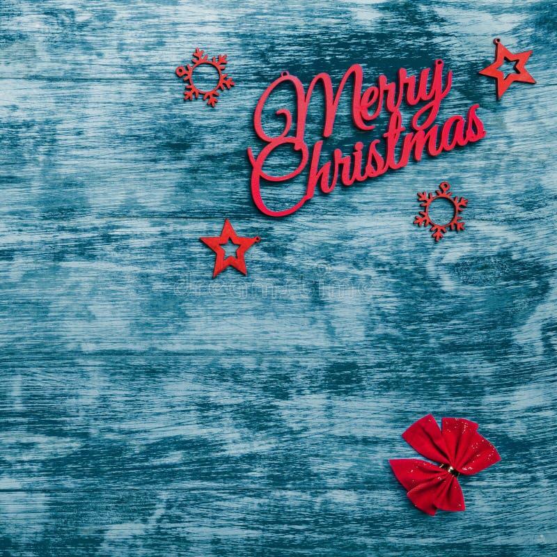 С Рождеством Христовым знак и handmade игрушки ели, с красной лентой в углах, голубая деревянная предпосылка, поздравительная отк стоковая фотография rf