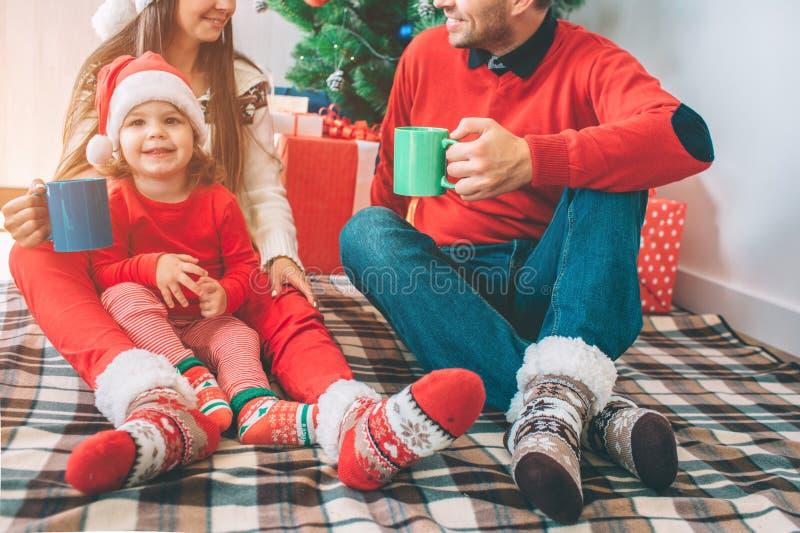 С Рождеством Христовым и с новым годом Взгляд отрезка человека и женщина сидят на одеяле с их ребенком Они держат чашки и смотрят стоковое фото rf