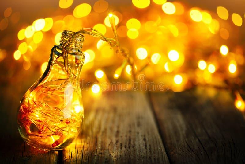С Рождеством Христовым и с новым годом Гирлянда рождества в стеклянном опарнике на деревянном столе Селективный фокус стоковое фото rf