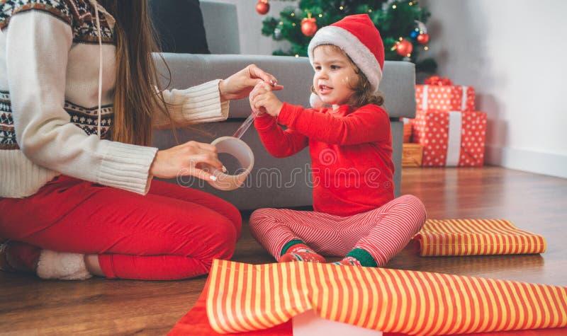 С Рождеством Христовым и с новым годом Девушка и молодая женщина сидят на поле Лента достигаемостей и касаний ребенка Женщина дер стоковое изображение rf