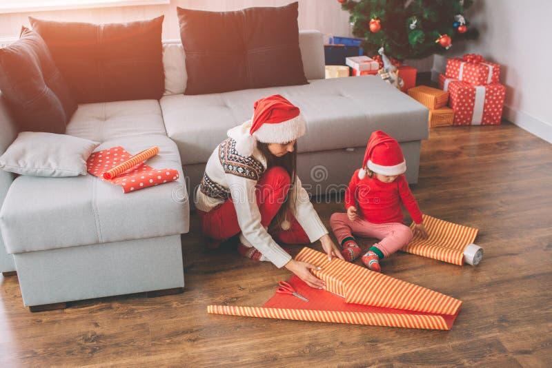 С Рождеством Христовым и с новым годом Изображение молодой женщины и ее daghter сидя на поле Взрослая коробка упаковки  стоковая фотография rf