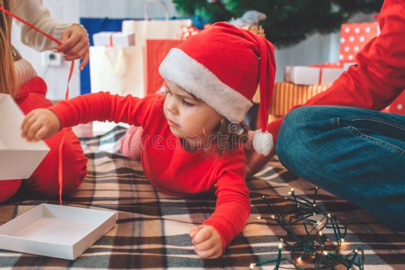 С Рождеством Христовым и с новым годом Изображение ребенк лежа на животе на одеяле Девушка касается белой коробке Взрослый держит стоковые фото