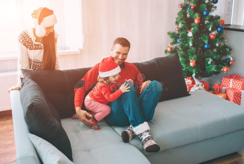 С Рождеством Христовым и с новым годом Изображение семьи Молодой человек сидит на софе с дочерью Они тратят tgether времени Женщи стоковая фотография rf