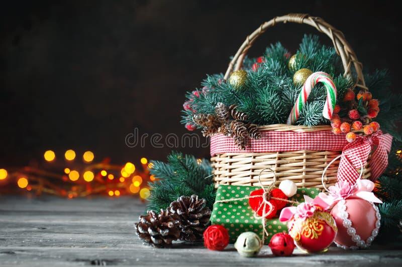 С Рождеством Христовым и с новым годом Корзина с игрушками рождества и подарками рождества на деревянной предпосылке стоковая фотография rf
