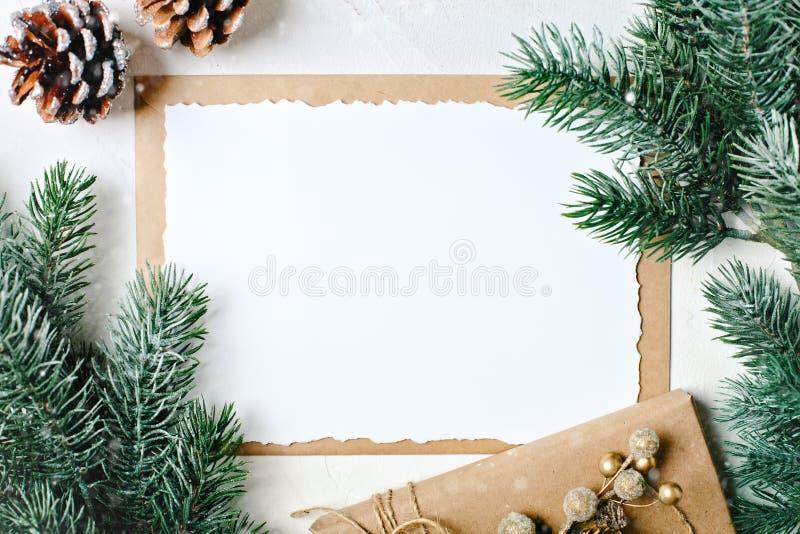 С Рождеством Христовым и с новым годом Модель-макет с открыткой и ветвями рождественской елки на белой предпосылке стоковые фотографии rf
