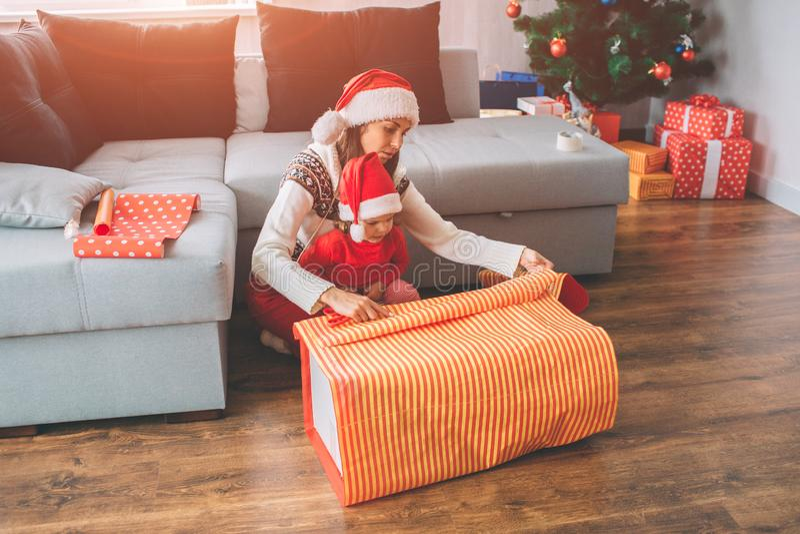 С Рождеством Христовым и с новым годом Молодая женщина и малая девушка сидят совместно Ребенок внутри на подоле ` s матери Они по стоковое изображение rf
