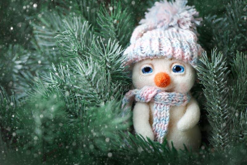 С Рождеством Христовым и с новым годом Небольшое положение снеговика игрушки в ветвях спруса Предпосылка с космосом экземпляра стоковые изображения
