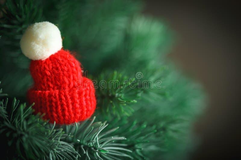С Рождеством Христовым и с новым годом Немногое связанная шляпа на рождественской елке Предпосылка с космосом экземпляра стоковое изображение