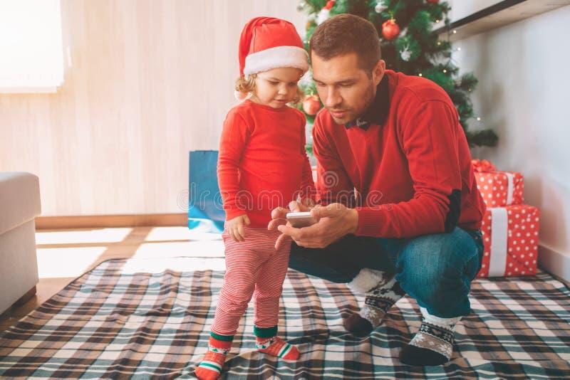 С Рождеством Христовым и с новым годом Отец и дочь стоят совместно Родительский мобильный телефон владением в руках Они оба взгля стоковое фото rf
