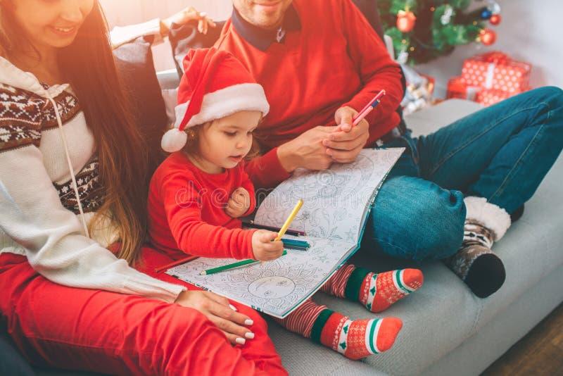 С Рождеством Христовым и с новым годом Отрежьте взгляд родителей сидя на софе с их ребенком Ребенк держит расцветку и стоковое фото