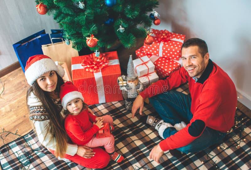 С Рождеством Христовым и с новым годом Праздничное изображение взрослых и девушка сидя на одеяле и смотрят вверх на камере челове стоковые фотографии rf