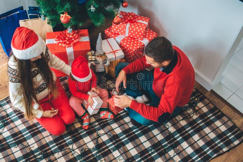 С Рождеством Христовым и с новым годом Ребенк сидит между родителями и открытым подарком Она сконцентрирована Гай держит красный  стоковая фотография rf