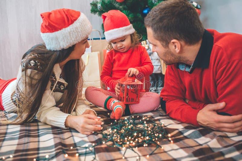 С Рождеством Христовым и с новым годом Сконцентрированный ребенк сидит между родителями Она держит красные фонарик и игру с ей Же стоковые изображения rf