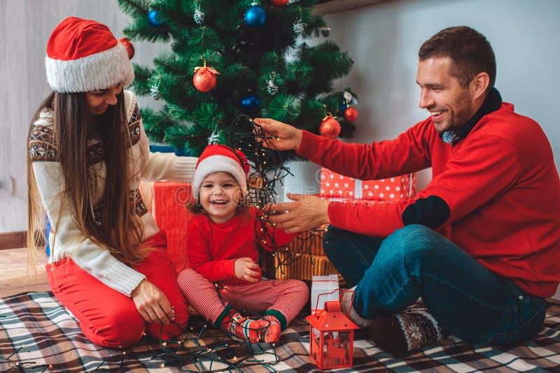 С Рождеством Христовым и с новым годом Счастливая малая девушка сидит между родителями и смеяться над Мать смотрит вниз Она носит стоковое фото