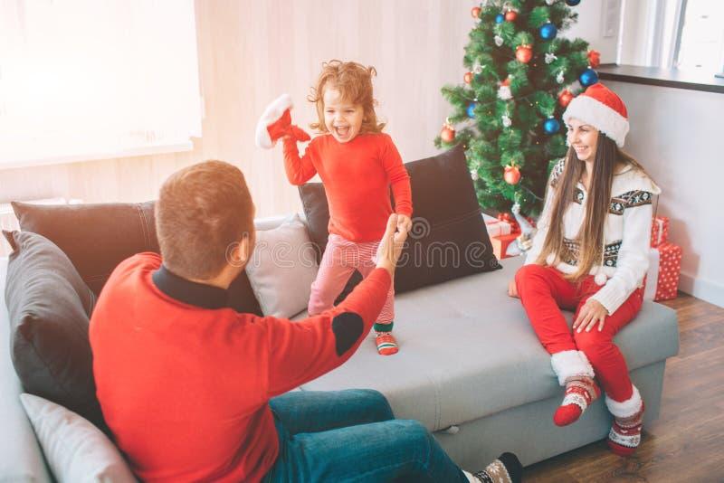С Рождеством Христовым и с новым годом Шаловливое изображение счастливого ребенка стоя на кресле и держа красную шляпу Она смотри стоковая фотография