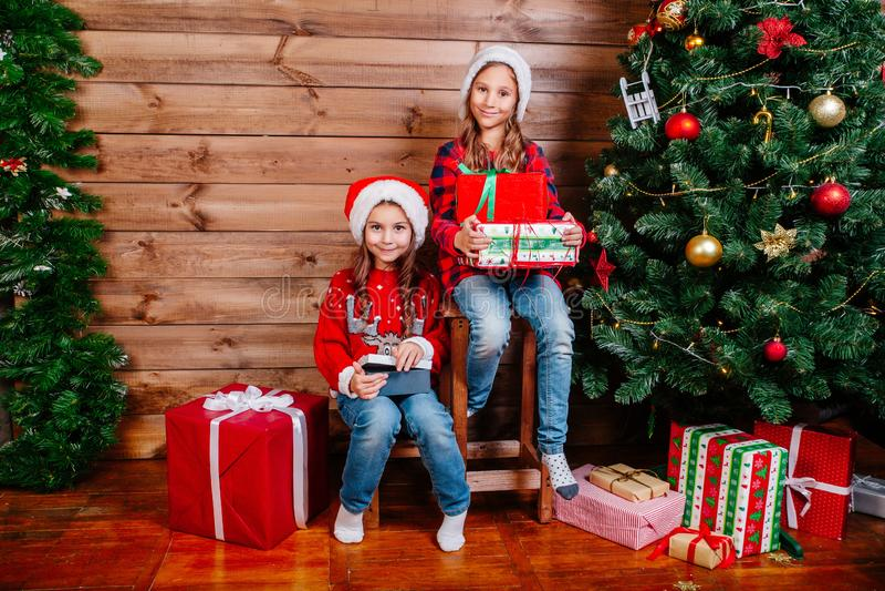 С Рождеством Христовым и счастливый праздник 2 милых девушки маленьких ребенка с присутствующими подарочными коробками около дере стоковые фотографии rf