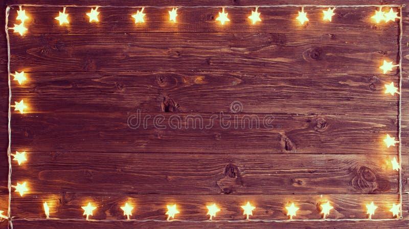 С Рождеством Христовым! Рамка светов рождества на деревянной предпосылке с космосом экземпляра стоковые фото