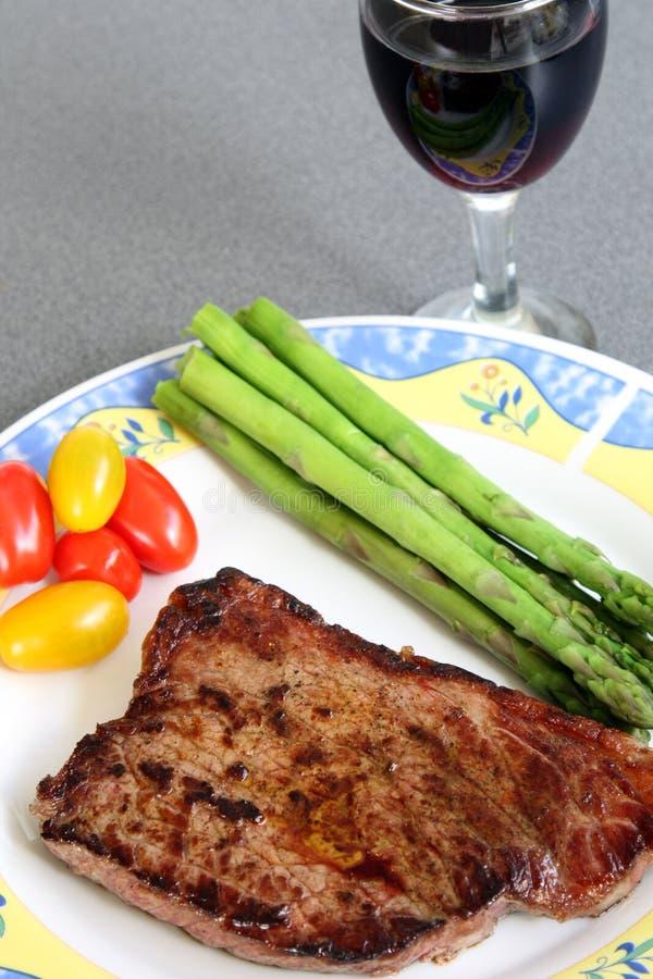 Служат часть средства зажарила стейк говядины с томатами, спаржей и стеклом красного вина стоковое изображение rf