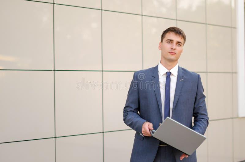 Случай в пути Уверенно и успешный бизнесмен держа компьтер-книжку стоковое фото