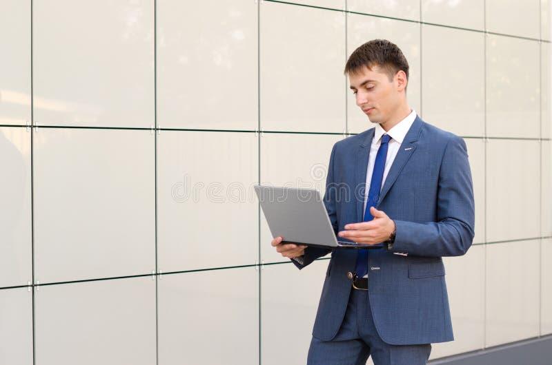 Случай в пути Уверенно и успешный бизнесмен держа компьтер-книжку стоковая фотография rf