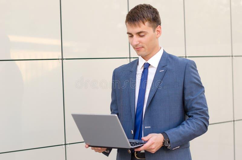 Случай в пути Уверенно и успешный бизнесмен держа компьтер-книжку стоковые фото