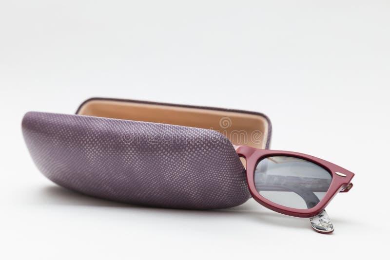 Случай и солнечные очки на белой предпосылке стоковая фотография