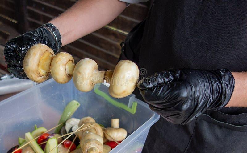 Сhef lagar mat champinjoner Mannen, i att laga mat likformign och handskar förbereder champignonsteknålar för att grilla Utvändig arkivbilder